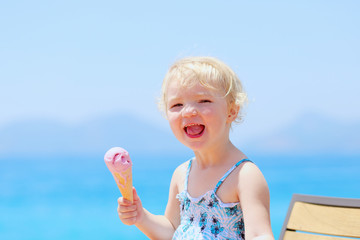 Happy little girl eating ice cream during summer vacations