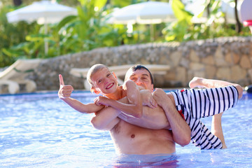 Father and teenage son having fun in outdoors swimming pool