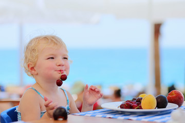 Happy little girl eating fruits in beach restaurant