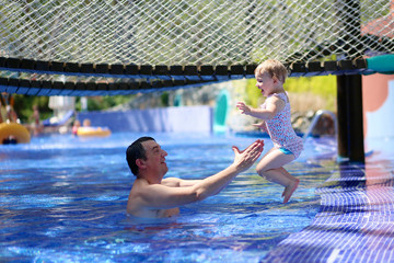 Active father having fun in swimming pool with his daughter