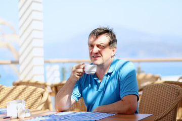 Man relaxing with cup of coffee in cafe during summer holidays
