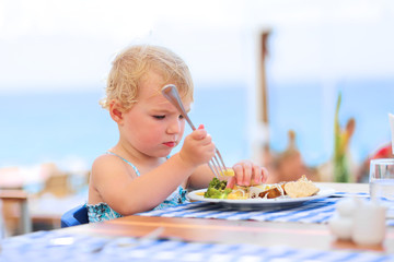 Cute little girl having dinner in restaurant with sea view