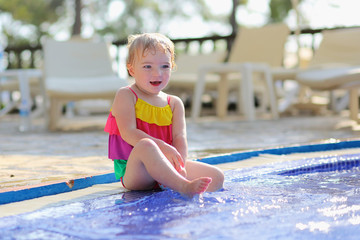 Happy little girl having fun splashing in swimming pool