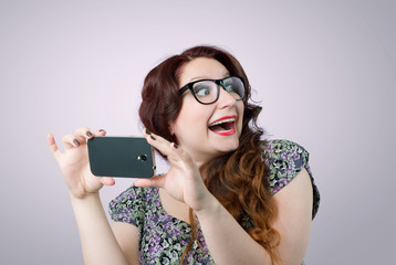 Funny happy lady with a smartphone on pink background