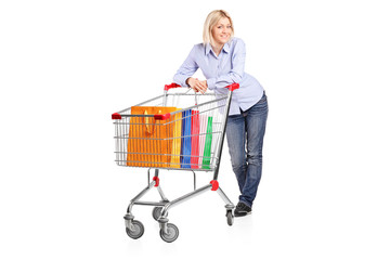 Blond female posing behind a shopping cart