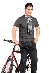 Fashionable young man standing by a bicycle