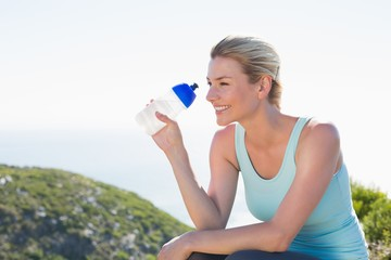 Fit blonde sitting at summit holding water bottle