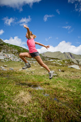 Young woman running and jumping in nature