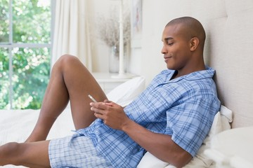 Happy man sitting on bed and texting on phone