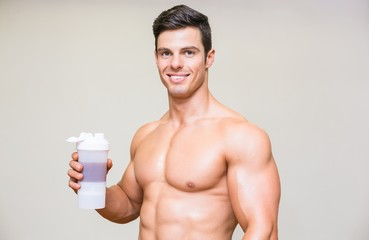 Close-up portrait of a sporty young man with protein drink