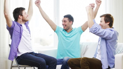 smiling male friends giving high five at home