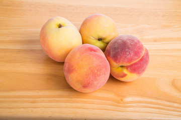 Four Fresh Peaches on a Wood Table