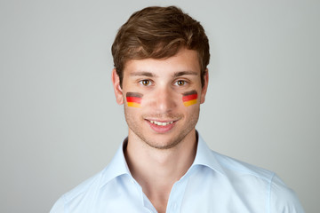 young handsome man with flag of germany painting at face