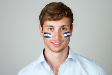 young handsome man with flag of Argentina painting at face