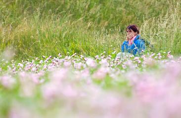 Donna seduta su prato fiorito