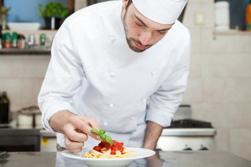 Male chef completing pasta.