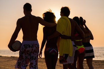 Group of multi ethnic friends walking on a beach against sunset
