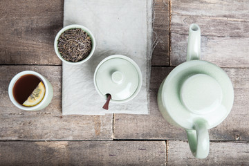 Tea set with tea crop, croissants, teapot and mug.