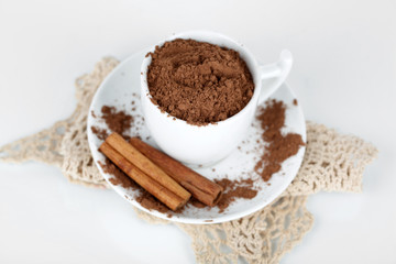 Cocoa powder in cup with saucer on napkin isolated on white