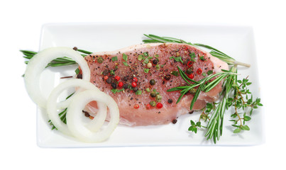 Raw meat steak with spices and herbs on plate, isolated on