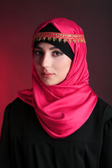 Beautiful muslim arabic woman on dark color background