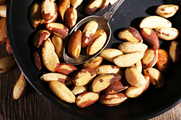 Tasty brasil nuts in pan, close up