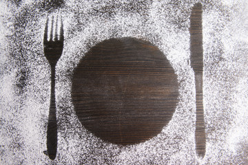 Imprint of cutlery  made of flour on table close-up