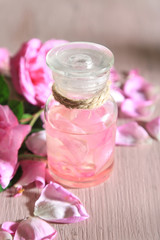 Rose oil in bottle on color wooden background