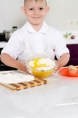 Cute young boy baking a cake