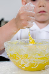 Little boy mixing cake ingredients
