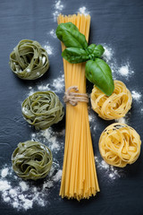 Raw colored tagliatelle, spaghetti and fresh basil, above view