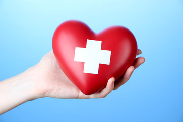 Red heart with cross sign in female hand, close-up,