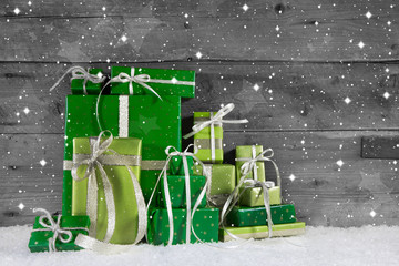 On wooden background many green christmas presents