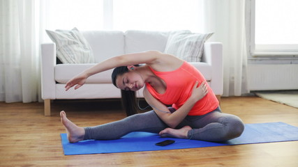 smiling teenage girl stretching on mat at home