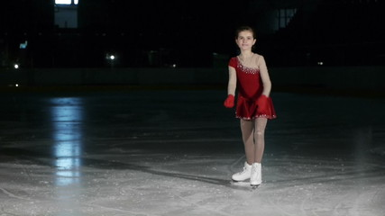 cute little ice skater girl smiling and bowing with grace