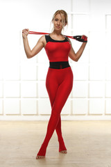 Sexy woman in a slinky red suit exercise fitness gym aerobics