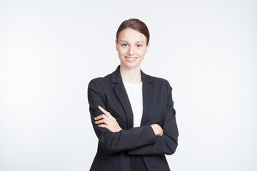 Smiling businesswoman with her arms crossed on white background