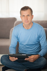 Portrait of mature man in sofa with tablet