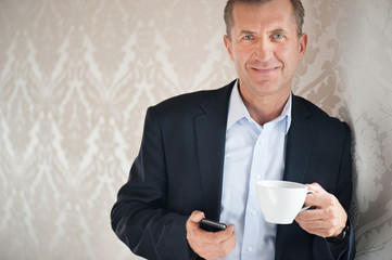 Man with mobile or smartphone and cup of coffee