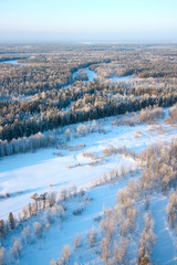 Top view of trees in hoar beside forest river in winter