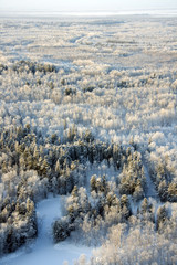 Top view of the snow-covered lowland nearby forest river