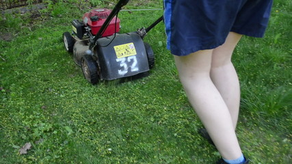 Speed up follow walking woman cutting lawn with grass cutter