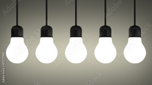 Hanging glowing tungsten light bulbs on gray