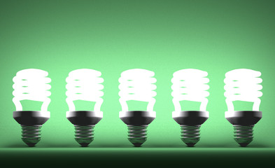Row of glowing spiral light bulbs on green
