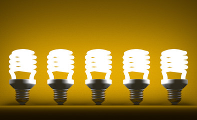 Row of glowing spiral light bulbs on yellow