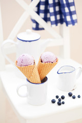 Blueberry ice cream in waffle cones, selective focus
