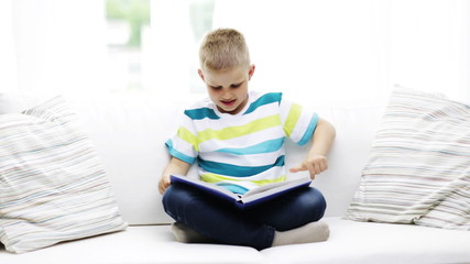 smiling little schoolboy reading book at home