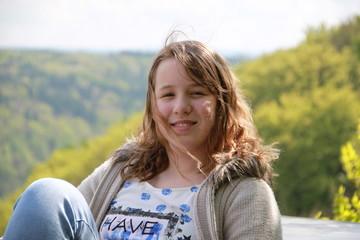 Fröhliches Mädchen pausiert auf Wanderung im Wald