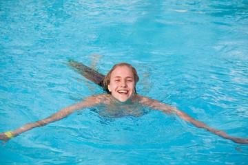 Молодая девушка плавает в бассейне
