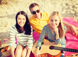 group of friends with guitar having fun on beach